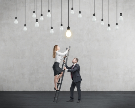 Businessman holds a ladder for the business lady. The concept of the teamwork and cooperation.